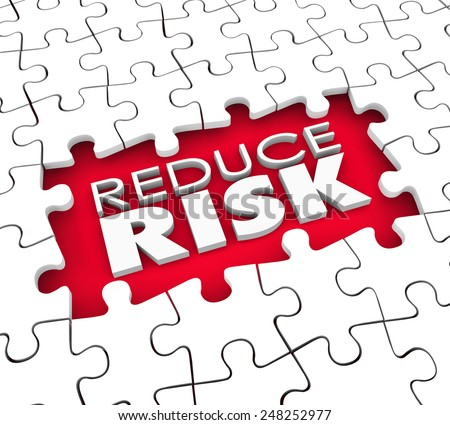 Reduce Risk words in the hold of a puzzle with missing pieces to illustrate the need to lower dangers and increase safety and security - stock photo