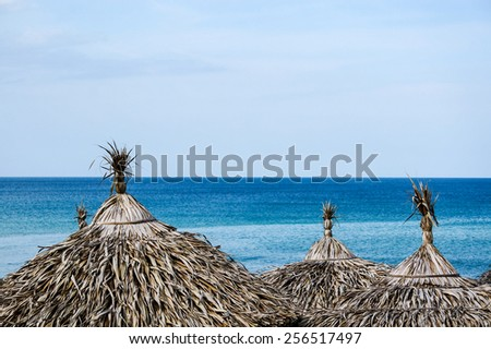 Reed beach umbrellas against a tropical blue ocean and sky in Vietnam - stock photo