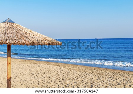 Reed umbrella on the beach to the seaside - stock photo