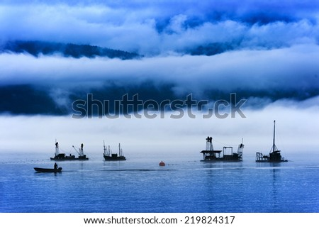 Reefnet Salmon Fishermen on a Foggy Day. Pacific salmon fishermen off of Lummi Island in the Puget Sound area of Washington State. Reefnetting is an old Indian method for catching salmon. - stock photo