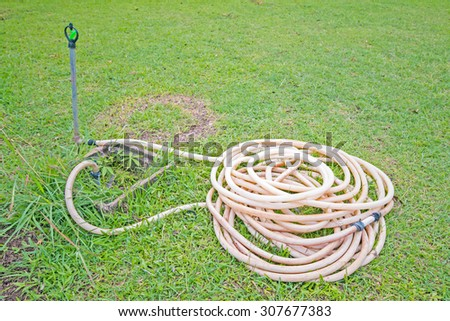 Reel of hose pipe and spraying head on grass with sprinkler - stock photo