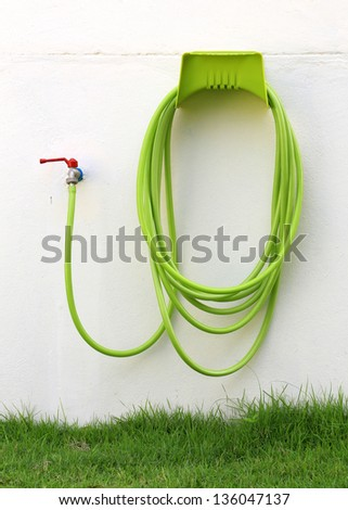 Reel of hose pipe and spraying head on the wall - stock photo