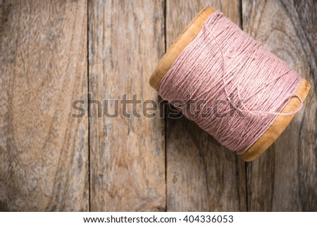 Reel pink yarn right side on wood background - stock photo