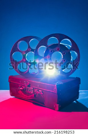 Reels of film on a old suitcase - stock photo
