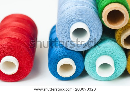 reels of thread on white table, not isolated - stock photo
