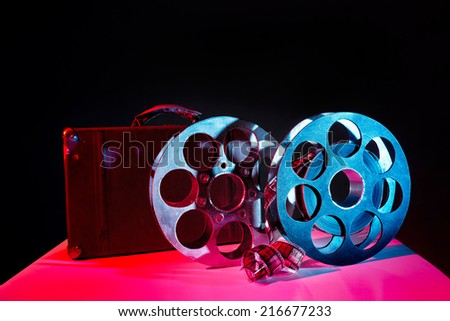 Reels with film and a old suitcase on the bright background - stock photo