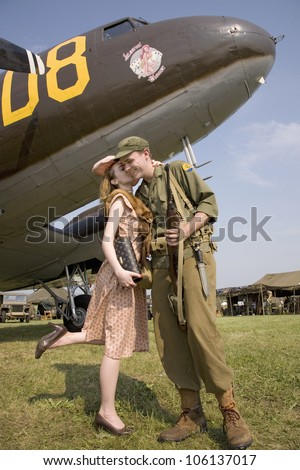 Reenactment of 1940s kiss of US soldier in front of World War II Bomber at Mid-Atlantic Air Museum World War II Weekend and Reenactment in Reading, PA held June 18, 2008 - stock photo