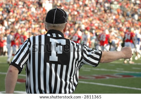 referee giving hand signal at a football game - stock photo