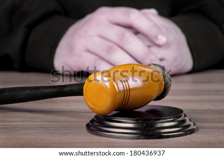 Referee hammer and a man in judicial robes in court - stock photo