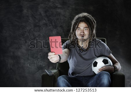 Referee watching the game on the tv showing the red card - stock photo