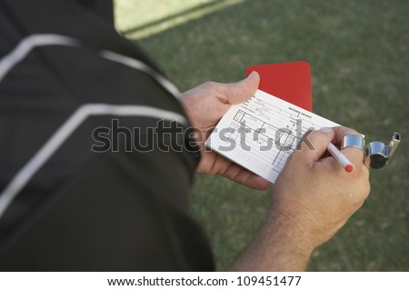 Referee writing in his report book while holding a red card - stock photo