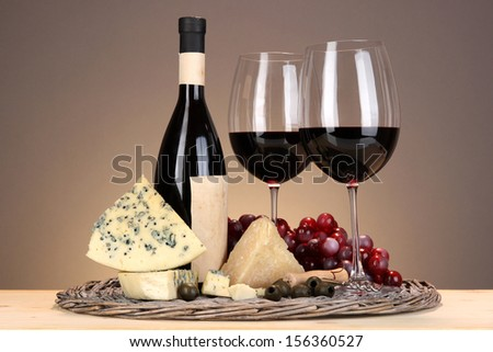 Refined still life of wine, cheese and grapes on wicker tray on wooden table on beige background - stock photo