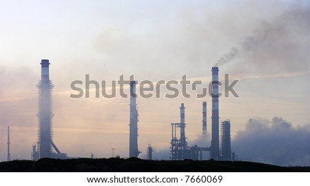 Refinery at dawn (first rays of the morning sun) - stock photo