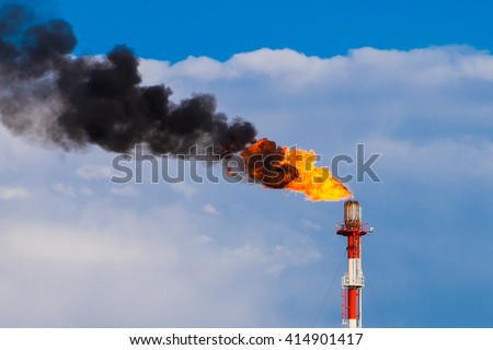 Refinery chimney with fire - stock photo