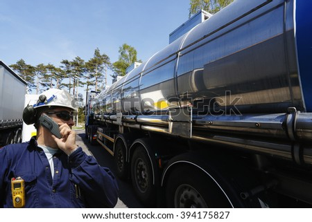 refinery worker filling large fuel-truck inside refinery, oil and gas transportation - stock photo