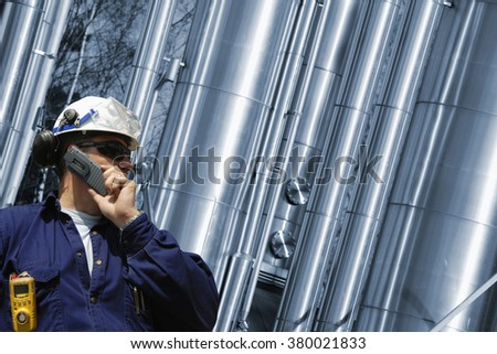 refinery worker with giant gas pipes in the background - stock photo