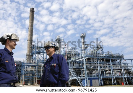 refinery workers and chemical plant in background - stock photo