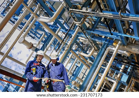 refinery workers and pipelines in full HDR colors - stock photo