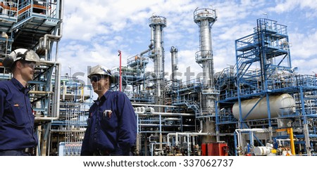 refinery workers inside large oil and gas petrochemical refinery - stock photo