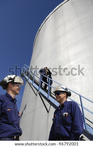 refinery workers with giant fuel storage towers in background - stock photo