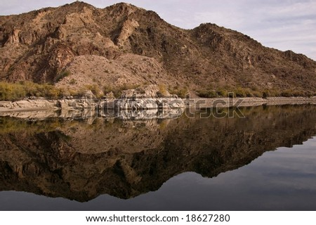 Reflected hill side along Black Canyon River - stock photo