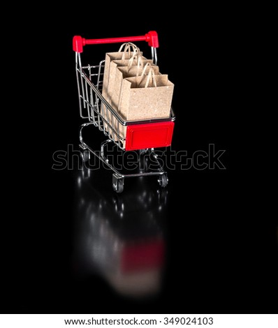 reflected shopping cart with paper bags is isolated on black background - stock photo