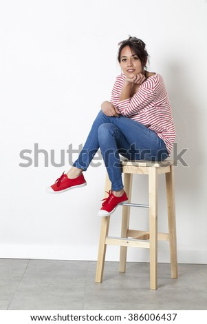 reflection concept - radiant young multi-ethnic female student sitting on a stool relaxing in thinking about her summer vacation, white background studio