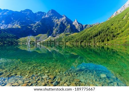 Reflection in green water mountain lake Morskie Oko, Tatra Mountains, Poland  - stock photo