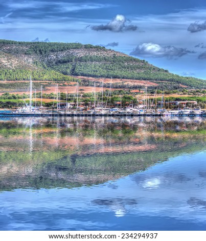 reflection in Porto Conte harbor, Sardinia. Processed for hdr tone mapping effect. - stock photo