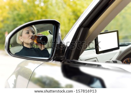 Reflection in the side view mirror of the car of an alcoholic female driver drinking as she drives along the road sipping directly from a bottle of spirits - stock photo