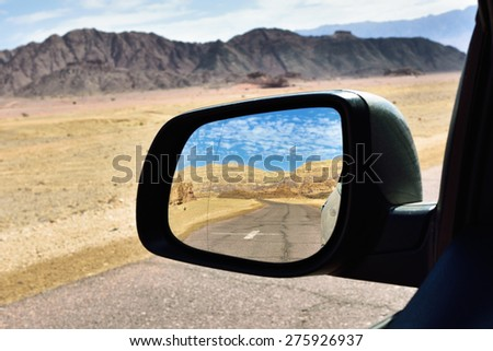 Reflection of a beautiful landscape and wriggling  road in the looking glass of a car. Travel concept - stock photo