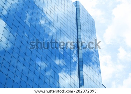 Reflection of a cloudy sky in glass wall of an office building - stock photo
