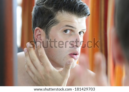 Reflection of an attractive man shaving in bathroom mirror - stock photo