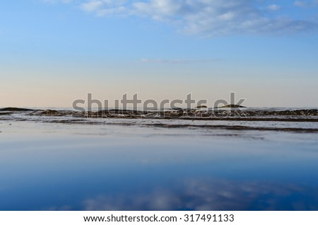 Reflection of blue sky on the surface of the ocean  - stock photo