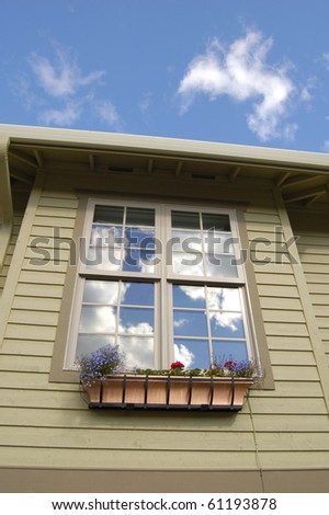 Reflection of clouds and sky in window of new home - stock photo
