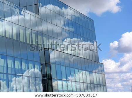 Reflection of clouds in a glass building - stock photo