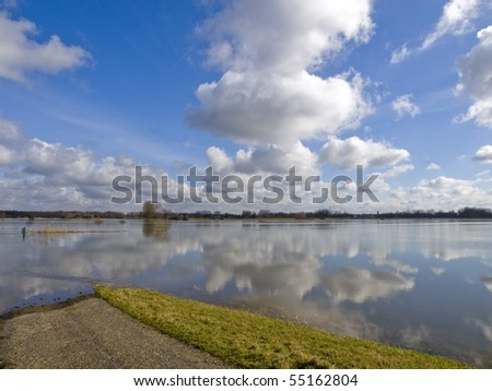 Reflection of clouds on a flood plains - stock photo