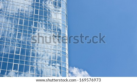 Reflection of clouds on the skyscraper made of glass and steel - stock photo