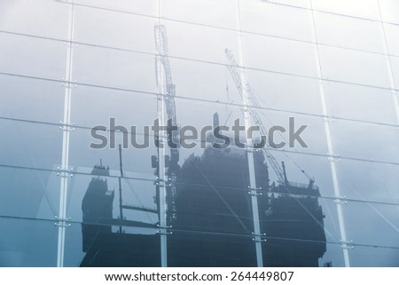 reflection of construction crane on mirror - stock photo