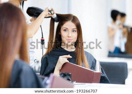 Reflection of hairdresser doing haircut for woman in hairdressing salon. Concept of fashion and beauty - stock photo