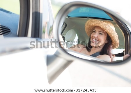Reflection of happy woman in rearview mirror of car - stock photo