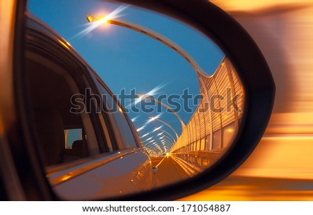 Reflection of high-speed road on car mirror - stock photo