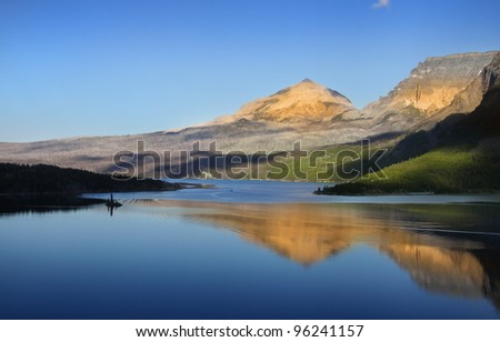 Reflection of hills in Saint Mary lake - stock photo