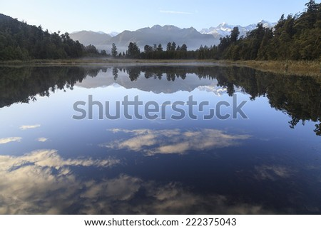 Reflection of Lake Matheson with Mount Cook and Mount Tasman as background, West Coast region, South Island, New Zealand. - stock photo