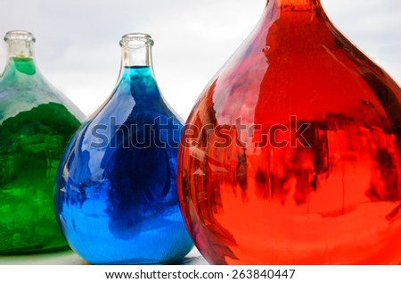 Reflection of medieval street in big dirty bottles with colored liquid. Cityscape in bottle glass. Selective focus on the reflection in right bottle. - stock photo