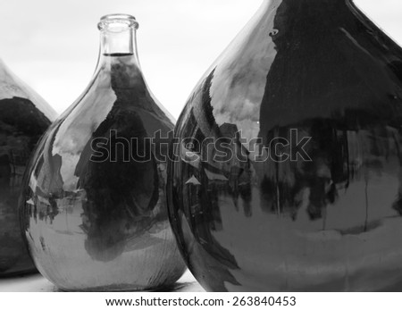 Reflection of medieval street in big dirty bottles with colored liquid. Cityscape in bottle glass. Black and white aged photo. Selective focus on the reflection in right bottle. - stock photo
