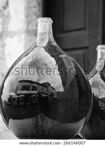Reflection of medieval town street in big dirty bottles with colored liquid. Cityscape in bottle glass. (Provence France) Black and white aged photo. Selective focus on left bottle. - stock photo