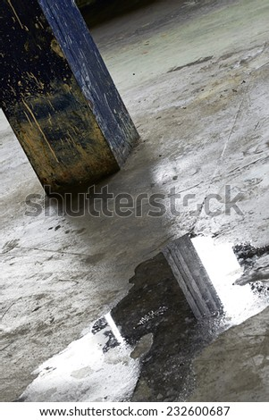 Reflection of pillar in water in an old factory - stock photo