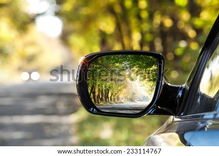 Reflection of  sunny autumn road at the car side mirrow. - stock photo