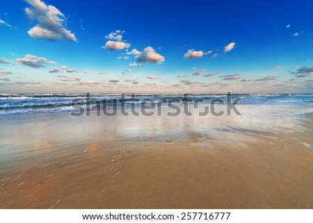 reflection of the sky in the sand beach - stock photo